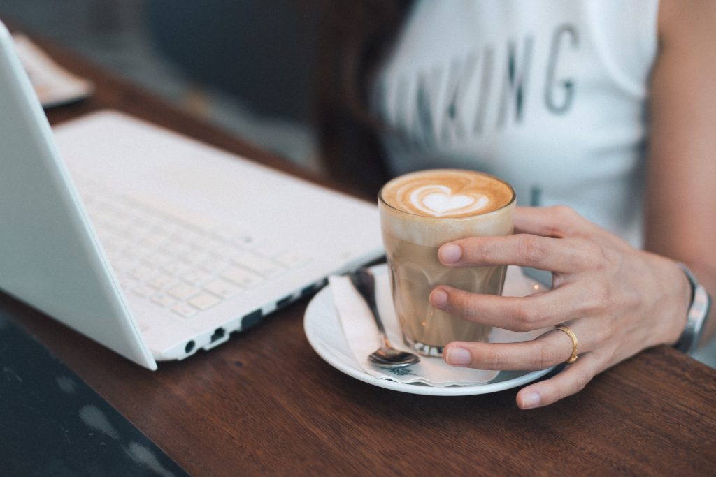 woman hand holding coffee latte with laptop on the wood desk vintage color